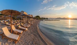 Sunbeds and umbrella on the beach at sunset time, Corfu Island, Greece. Sunbeds and umbrella on the beach at sunset time on Corfu Island, Greece stock image