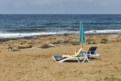 Sunbeds and umbrella for relaxation on the sea beach Stock Photo