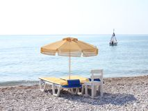 Sunbeds and umbrella. On the beach royalty free stock image