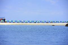 Sunbeds with umbrellas at the beach on blue background Royalty Free Stock Images