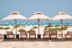 Sunbeds and umbrellas at the beach of luxury hotel Royalty Free Stock Photo