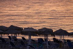 Sunbeds With Umbrellas on the Beach in the Morning, Moments Befo. Re Sun Goes Up Nea Vrasna, Greece Royalty Free Stock Image