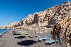 Sunbeds and umbrellas at beach near white rock of Santorini island, Greece Stock Photos