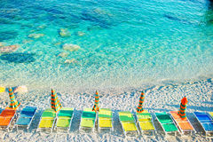 Sunbeds and umbrellas at beautiful european seashore in Monterosso in Italy, Cinque Terre, Liguria Royalty Free Stock Photo