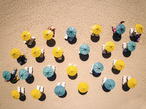 Sunbeds and umbrellas on hot sand Stock Images