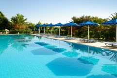 Sunbeds with umbrellas and palm trees around the pool, Greece. stock photos