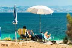 Sunbeds and umbrellas (parasols) on the beach in Corfu Island, Greece Stock Photos