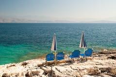 Sunbeds and umbrellas (parasols) on the beach, Corfu Island, Greece Royalty Free Stock Photos