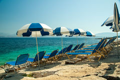 Sunbeds and umbrellas (parasols) on the beach in Corfu Island, Greece Royalty Free Stock Photo