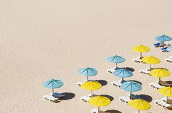 Sunbeds with umbrellas on the sandy beach. Isolated yellow and blue sunbeds with umbrellas on the sandy beach stock photo