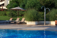 Sunbeds, umbrellas and shower near the pool. Royalty Free Stock Photography