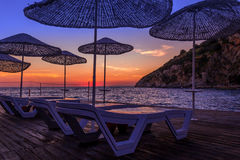 Sunbeds and umbrellas at sunset royalty free stock photography