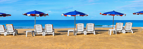 Sunbeds and umbrellas on a tropical beach. White sunbeds and umbrellas on a tropical beach - panorama Royalty Free Stock Image