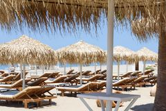 Sunbeds and umbrellas on tropical beach resort Stock Images