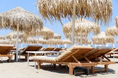Sunbeds and umbrellas on tropical beach resort Stock Photos