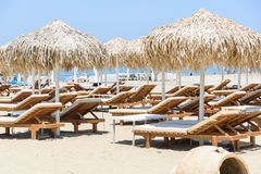 Sunbeds and umbrellas on tropical beach resort Royalty Free Stock Photo