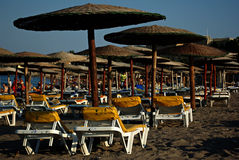 Sunbeds and Umbrellas. Yellow sunbeds and wooden umbrellas at sandy beach lit by late afternoon sun Stock Photos