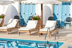 Sunbeds und Regenschirme nahe dem Pool Stockfotografie