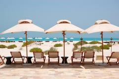 Sunbeds und Regenschirme am Strand des Luxushotels Lizenzfreies Stockfoto