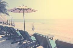 Sunbeds und Sonnenschutz, Regenschirmstrandstuhl auf dem Strand Weinlesefilterfarbe Stockbilder