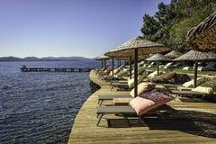Sunbeds und sundshades auf einer hölzernen Plattform über dem Meer unter klaren blauen Himmeln Lizenzfreie Stockfotos
