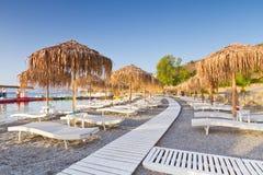 Sunbeds under ett slags solskydd på den offentliga stranden av Crete Royaltyfri Foto