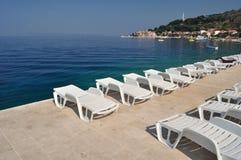 Sunbeds vacíos en la playa de Podgora Imagen de archivo libre de regalías