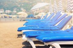 Sunbeds vazios com os colchões azuis no Sandy Beach Imagens de Stock Royalty Free