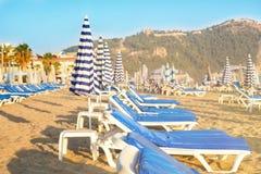 Sunbeds vazios com os colchões azuis no Sandy Beach Imagem de Stock Royalty Free