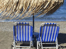 Sunbeds at Vlichada beach, Santorini, Greece. Stock Photo