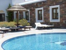 Sunbeds y choza por la piscina Foto de archivo libre de regalías
