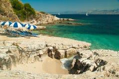 Sunbeds y paraguas (parasoles) en la playa en la isla de Corfú, Grecia Imagen de archivo