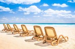 Sunbedschaise-longue bij tropisch leeg strand en turkooise overzees Stock Foto