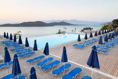 与sunbeds的游泳池在Mirabello海湾 免版税库存照片