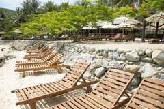 Sunbedsna på stranden med palmträd och havet Arkivfoto