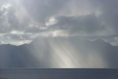 Sunbeams in rain storm. Light to dom of darkness. Royalty Free Stock Photos