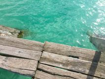 Sunbleached dock bordering the clear waters. Sun-bleached dock bordering the clear-blue waters Lago Bacalar in Mexico with the sun reflecting up Royalty Free Stock Photos