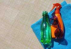 Sunblock bate, las gafas de sol y pequeña botella con agua y una toalla de playa azul Imagen de archivo libre de regalías