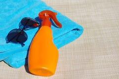 Sunblock bate, las gafas de sol y pequeña botella con agua y una toalla de playa azul Fotografía de archivo libre de regalías