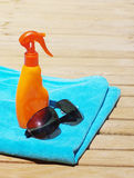 Sunblock cream, sunglasses and small bottle with water and a blue beach towel. Royalty Free Stock Photos