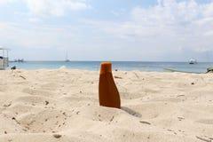 Sunblock flaska på stranden Arkivbild