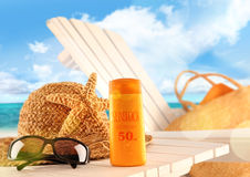 Sunblock lotion and beach items on table Royalty Free Stock Photo