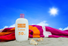 Sunblock lotion and towel Royalty Free Stock Images