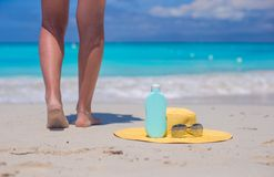 Sunblock, straw hat, sun glasses and close up female legs on white beach Royalty Free Stock Photos