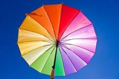 Sunblock via kleurrijke regenboogparaplu Stock Fotografie