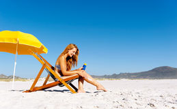 Sunblock woman. Beautiful young woman apllying sunblock to her legs while sitting on a beach in summer Royalty Free Stock Images