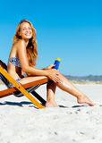 Sunblock woman. Beautiful young woman apllying sunblock to her legs while sitting on a beach in summer Royalty Free Stock Photo