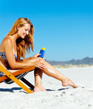 Sunblock woman. Beautiful young woman apllying sunblock to her legs while sitting on a beach in summer Stock Photography