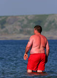 Sunburn Alert. Overweight man wearing bright red swimming trunks, paddling in the sea and heavily sunburnt Stock Photography