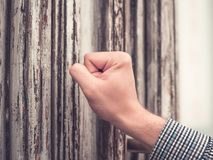 Sunburned hand of a man in a plaid shirt pounding his fist in the old and shabby front door. royalty free stock photography